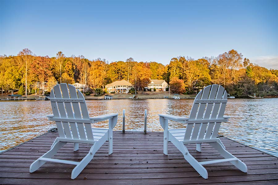 Private Client Insurance - Two Adirondack Chairs On Dock Overlooking Quiet Lake